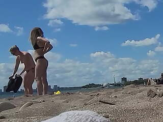Topless girls at Toronto unfold beach.